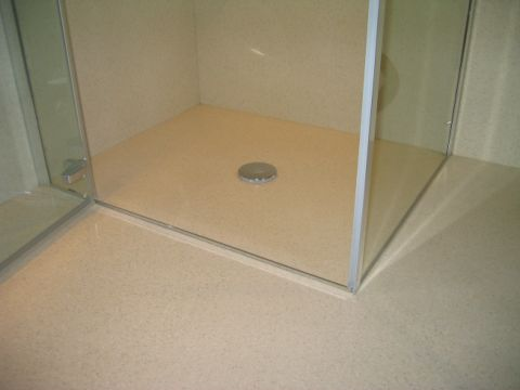 shower cubicle in corner of wet room